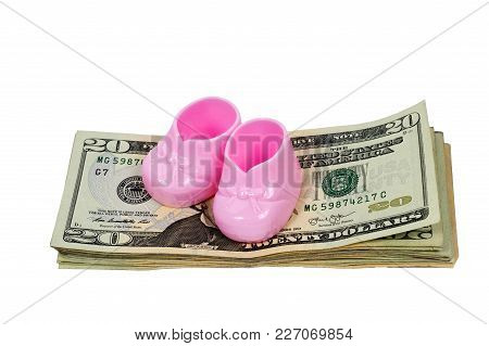 Horizontal Shot Of A Pair Of Pink Plastic Baby Booties Sitting On A Stack Of Twenty Dollar Bills On