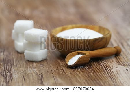 Sugar Cubes And Salt In Wooden Bowl