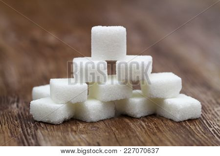 Stack Of White Sugar Cubes On Wooden Surface