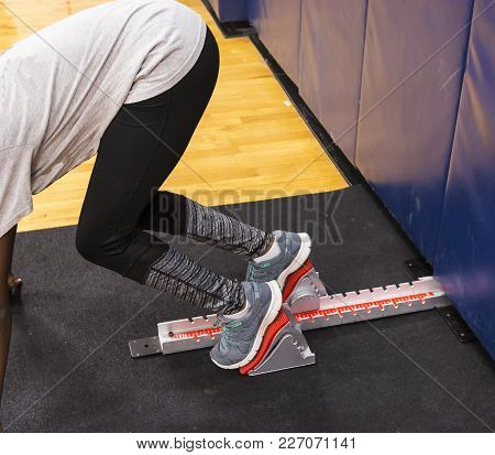 A High School Sprinter Practicing Coming Out Of The Blocks During An Indoor Practice Seccion In A Gy
