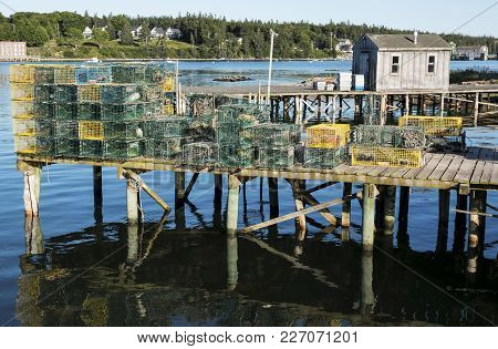 A Pier Over Bass Harbor In Maine Has Many Yellow And Green Lobster Traps Stacked And Ready To Be Put