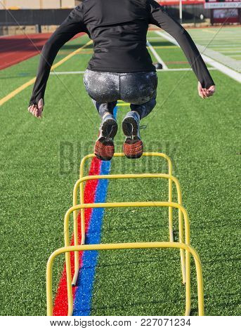 A High School Track And Field Sprinter Is Jumping Over Yellow Banana Hurdles For Strength And Stabil