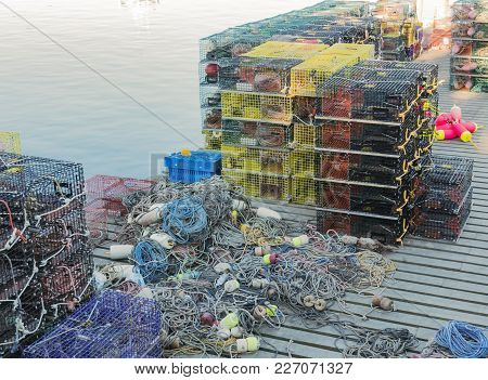 Many Lobster Traps Stacked On A Pier With Rope And Bouys Ready To Be Put To Work.