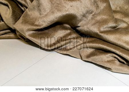 Soft Beige Blanket Folds Against White Surface