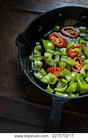 Green Pepper And Chili On A Cast-iron Frying Pan Closeup Vertical