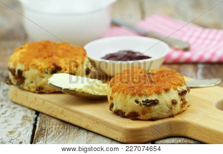 English Scones With Raisins On Wooden Board, Clotted Cream And Jam