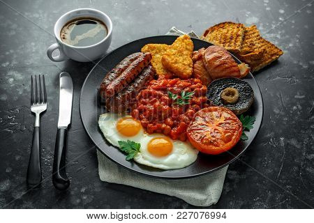 Full English Breakfast With Bacon, Sausage, Fried Egg, Baked Beans, Hash Browns And Mushrooms In Bla