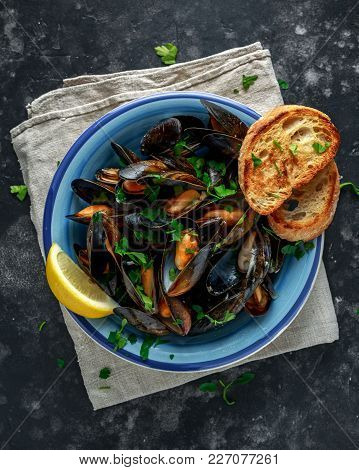 Mussels In Garlic Butter Sauce Served With Parsley, Toast And Lemon.