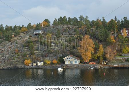 Small Island In Sweden Baltic Sea With Nice Summerhouse Close To Water Or On Hillside, Boats In Autu