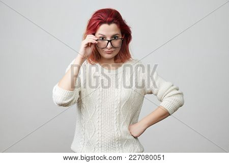Portrait Of Young Woman In White Sweater With Confused And Gloomy Expression, Correcting Glasses And