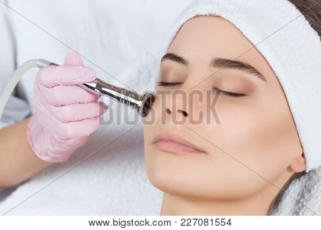 The Cosmetologist Makes The Procedure Microdermabrasion Of The Facial Skin Of A Beautiful, Young Wom