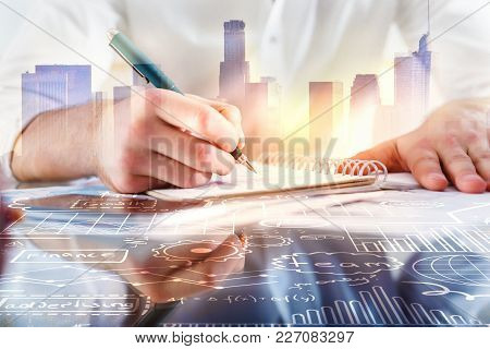 Close Up Of Businessman Hands Drawing Business Sketch In Notepad On Abstract City Background With Su