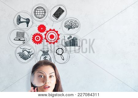 Portrait Of Surprised Young European Woman With Magnifier On Concrete Background With Business Sketc