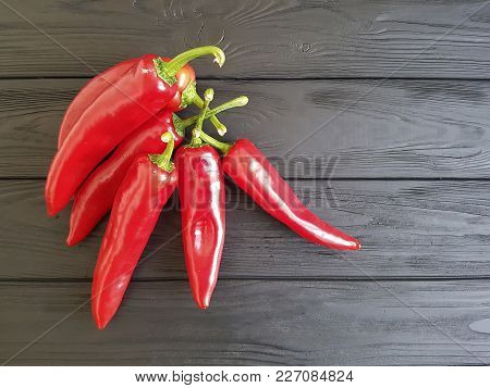 red pepper on a black wooden copy space, macro photography, wood, border,