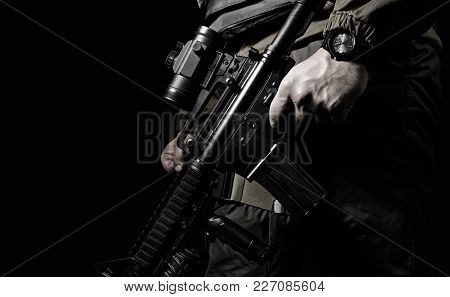 Closeup Black And White Photo Of Equipped Swat Soldier Holding A Rifle Profile View.