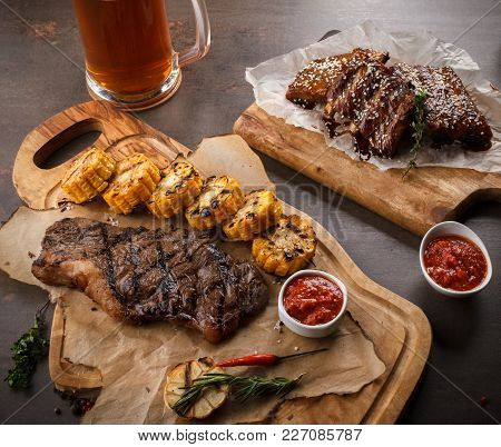 Juicy Steak On The Grill With Rosemary, Garlic, Chili And Corn On The Grill And Bread On The Wooden