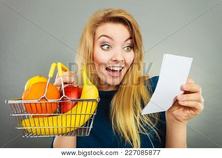 Happy Woman Holding Shopping Basket With Fruits Looking At Bill Receipt, Enjoying Low Prices.