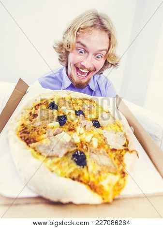 People, Italian Cuisine Concept. Young Funny Bearded Man Eating Hot Fresh Pizza. Delicious Fast Food