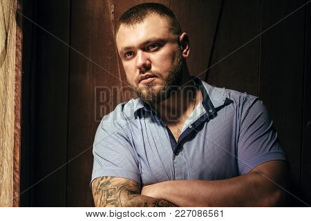 Brutal Bearded Man With A Tattoo On His Arm, A Portrait Of A Man In Dramatic Light Against A Brown W