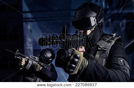 Photo Of A Swat Soldiers Posing With Automatic Rifles On A Night City Background.