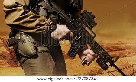 Photo Of A Soldier In Military Outfit Holding A Gun And Bulletproof Vest On Orange Desert Background