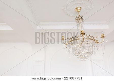 Expensive Interior. Large Electric Chandelier Made Of Transparent Glass Beads. White Ceiling Decorat