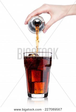 Female Hand Pouring Cola Soda Drink From Bottle To Glass  With Ice Cubes On White Background
