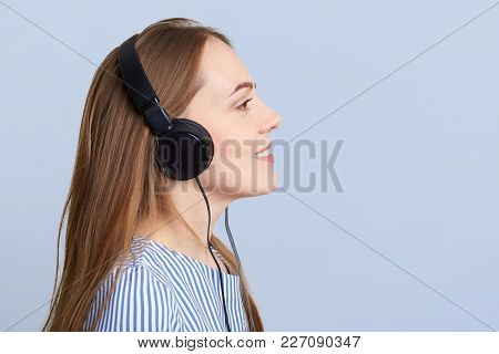 Sideways Portrait Of Adorable Young Female With Headphones Listens Favourite Song In Playlist, Uses