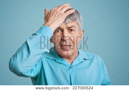 Forgetful Handsome Elederly Wrinkled Man In Blue Shirt, Keeps Hand On Head, Feels Desperately As For
