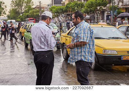 Policeman Checks Driver's License Of Driver, Tehran, Iran.