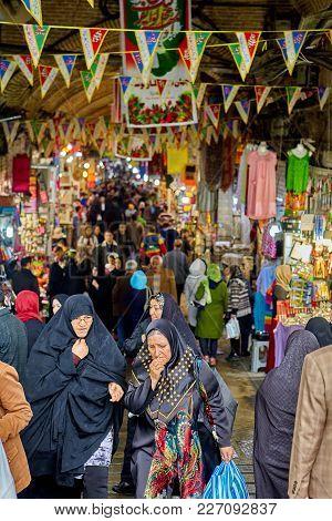 Tehran, Iran - April 29, 2017: Buyers Walk Around The Big Iranian Bazaar Between Tents With Clothes
