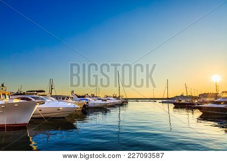 Luxury Yachts, Sailing And Motor Boats Docked In Sea Port At Sunset. Marine Parking Of Modern Motorb