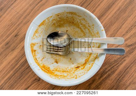 Top View Of Empty Bowl After Eating On Wooden Table Background.