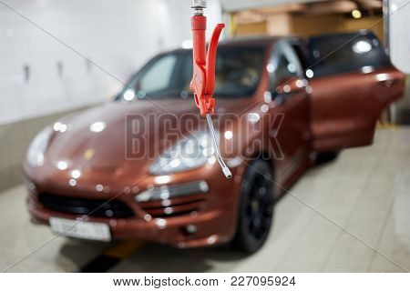 Syringe for water at car cleaning station, car at background.
