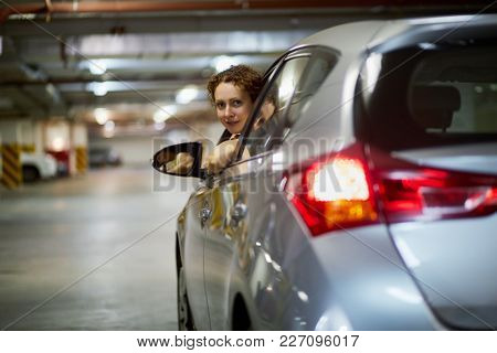 Young smiling woman looks out from driver window of silvery car at underground parking.