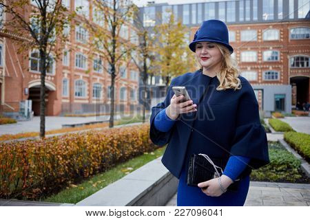 Smiling blonde woman in blue suit and hat walks in inner yard of house of red brick.