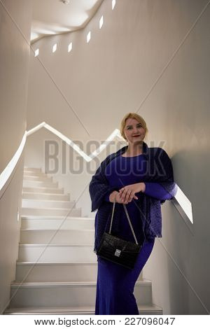 Blonde woman in blue dress stands on stairs leaning to wall.
