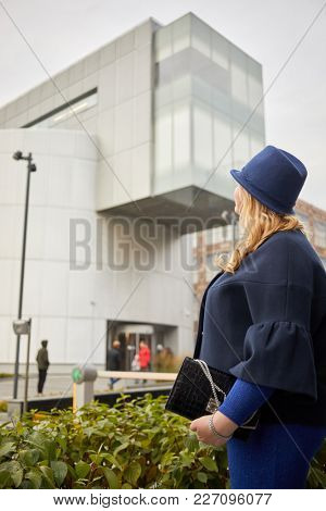 Blonde woman in blue suit and hat stands looking at silvery building.