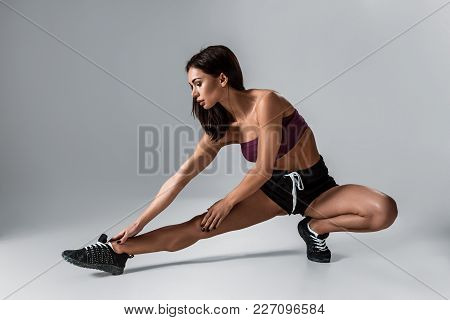 Beautiful Brunette Woman Stretching Her Legs, Warm Up On Grey Background. Young Woman In Sports Shor
