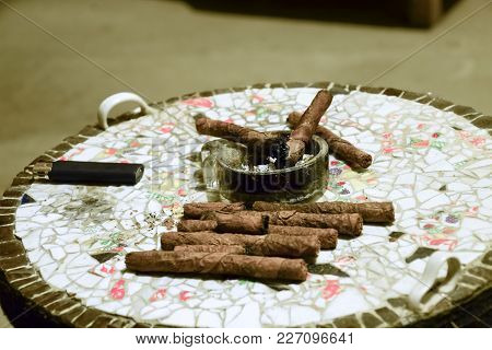 Homemade Cigars From Leafy Tobacco Leaves On A Ceramic Table. Ashtray And Cigars.