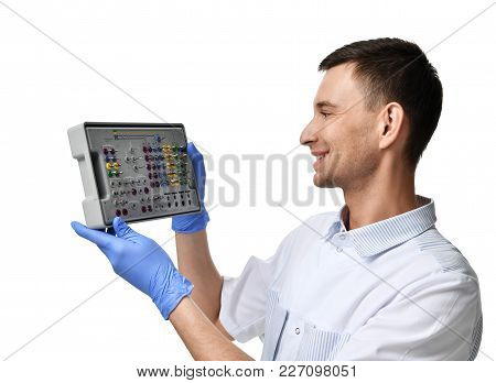 Young Doctor Dentist Hold Tapered Implant Surgical Tray Isolated On White Background
