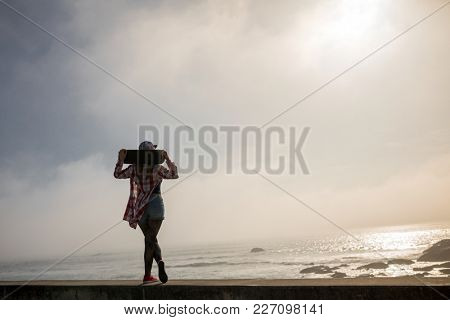 Silhouette of skater girl standing with skateboard looking to the sea