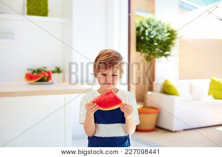 Cute Young Boy, Kid Eating A Piece Of Ripe Watermelon At Home Kitchen