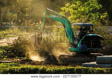 Mini Excavator Working On Dusty Soil In The Flied