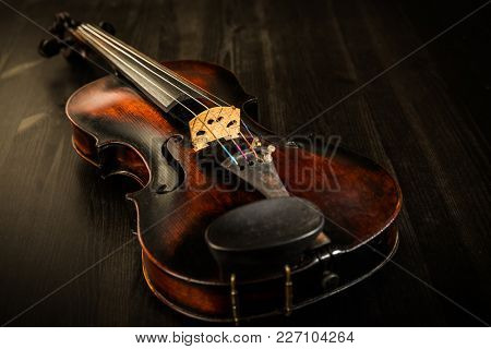 Old violin in vintage style on wood background