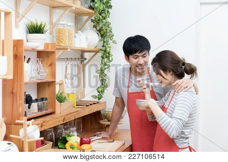 Happy Asian Young Couple Make Cooking In Kitchen, Man Looking And Smilling To Woman, Wife Preparing