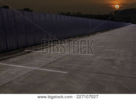 Empty Parking Car With Metal Sheet Wall At Sunset