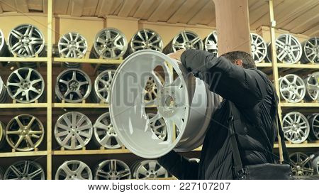 The Man Buys Alloy Wheels In His Shop For His Car. He Takes A Disc Out Of The Box And Looks At It. T