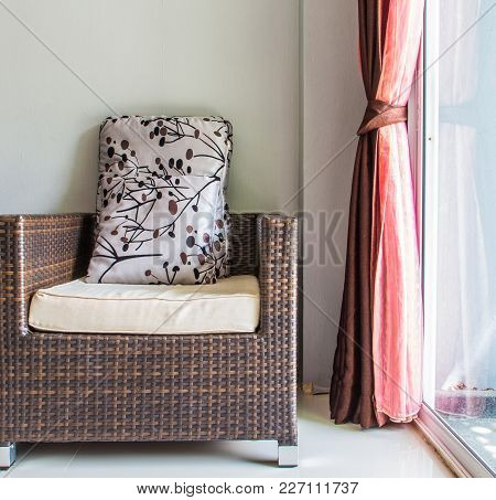 Rattan Chair Near Glass Door With Red Blinds In Hotel Room