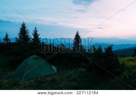 Picturesque summer landscape with colorful sunrise on Carpathian mountains. Lush green forest from pine tree on backgound. Travel concept